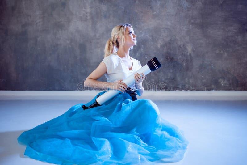 Sonhos do futuro, conceito da jovem mulher A menina olha acima e usa um telescópio fotos de stock royalty free