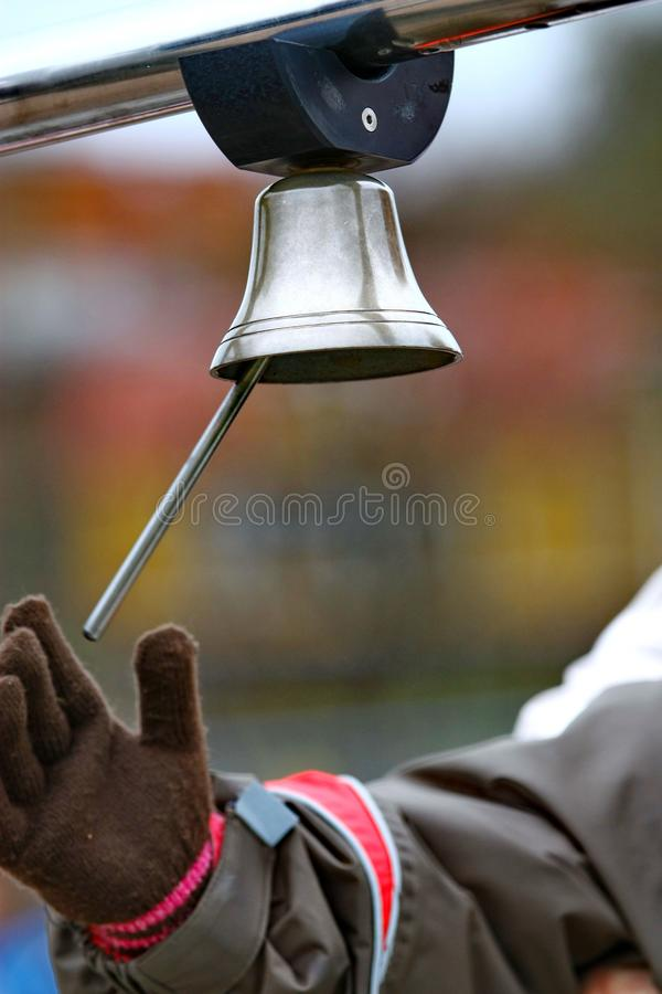 Sonido de una campana La mano en guante suena Bell imagenes de archivo