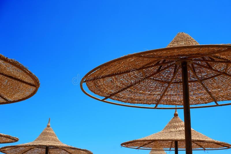 Sonnen-schützende Weidenregenschirme auf dem Strand gegen den Himmel, das Konzept von Sommertourismus lizenzfreie stockbilder