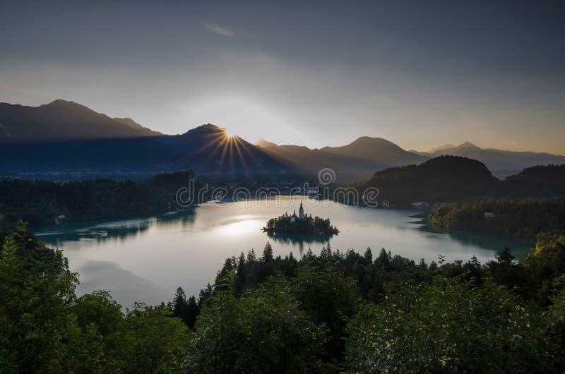 Sonnenaufgang über ausgeblutetem See mit Kirche St. Marys der Annahme auf der kleinen Insel Verlaufen, Slowenien, Europa stockfotografie