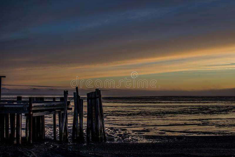 Sonnenaufgang über Bristol Bay vom Dock bei Ekuk Alaska bei Ebbe stockfotos