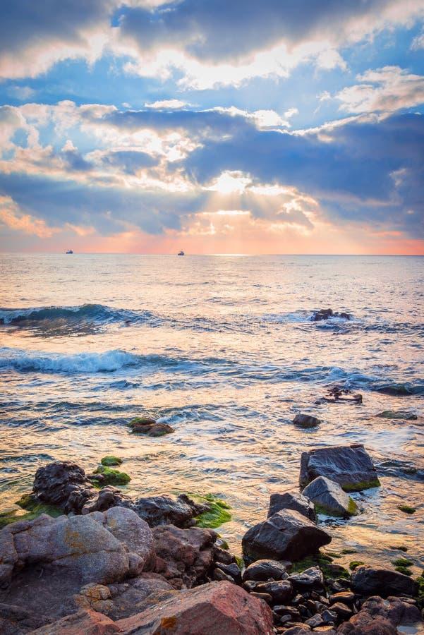 Sonnenaufgang über einem felsigen Strand Bunte Wolken, die im Meer sich reflektieren lizenzfreies stockbild