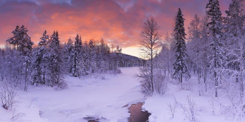 Sonnenaufgang über einem Fluss im Winter in finnischem Lappland stockbilder