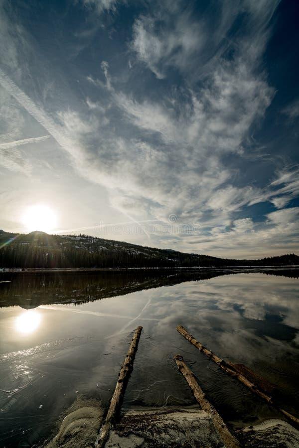 Sonnenaufgang über einem hoher Gebirgssee im Winter mit Wolken und refl stockfotos