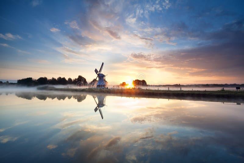 Sonnenaufgang über niederländischer Windmühle und Fluss stockbilder
