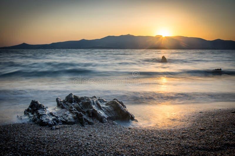 Sonnenaufgang auf Antiparos-Insel, Felsen und Strand im Vordergrund, Paros-Insel im Hintergrund Die Kykladen Griechenland stockbild