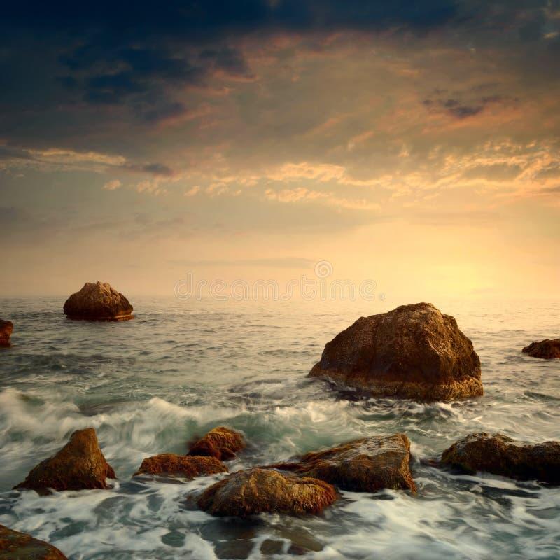 Sonnenaufgang auf felsiger Seeküste stockbilder