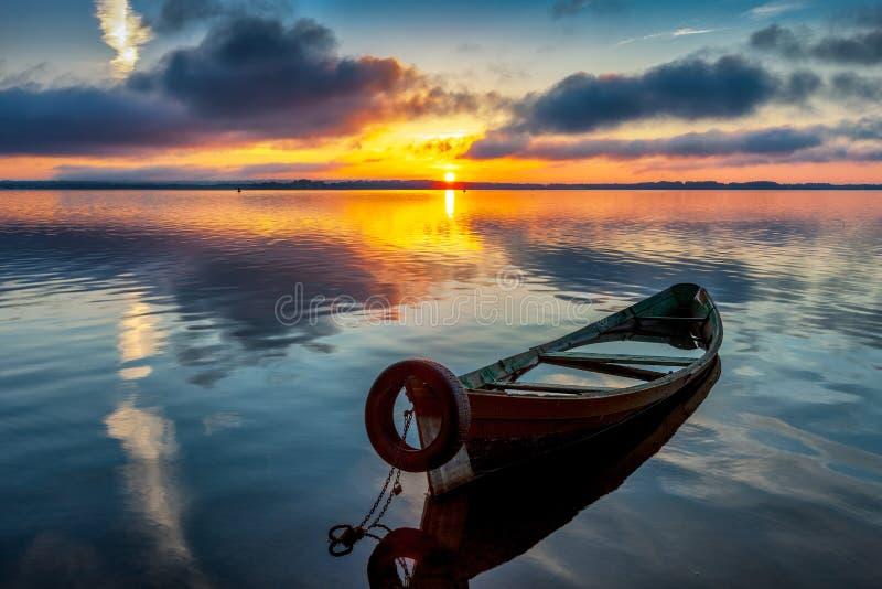 Sonnenaufgang auf See Seliger mit einem alten Boot im Vordergrund lizenzfreie stockbilder