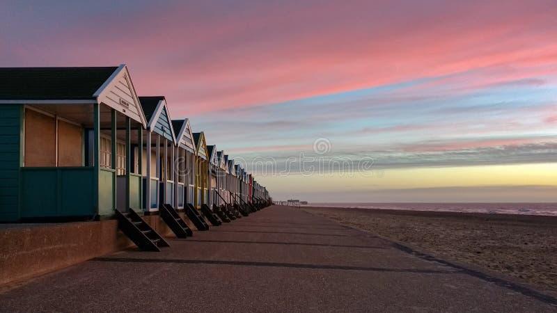 Sonnenaufgang, der auf bunten Strandhütten in Southwold, Suffolk, England glänzt stockfotos