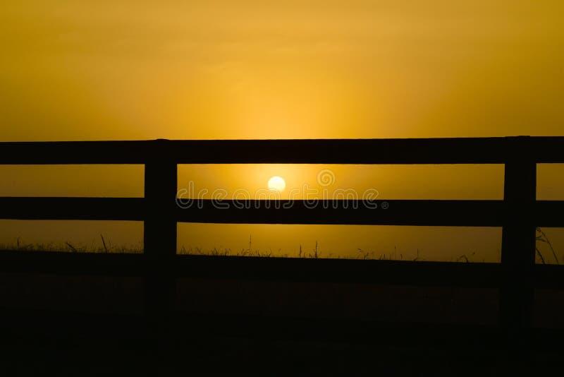 Sonnenaufgang hinter dem Zaun stockfoto