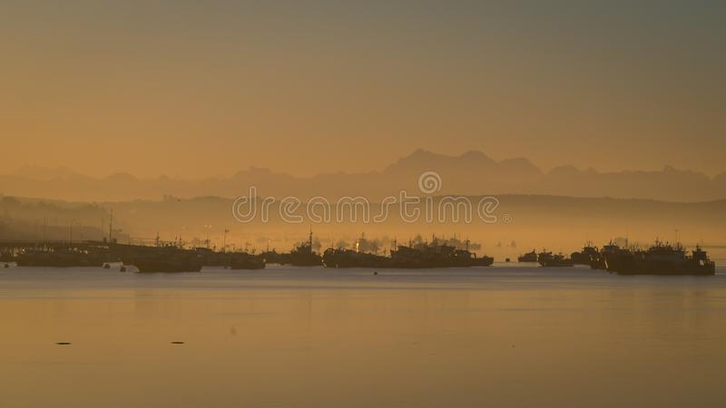 Sonnenaufgang im Hafen von Quellon in Chiloe-Insel stockfotos