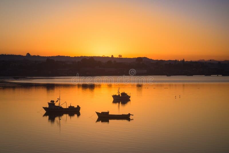 Sonnenaufgang im Hafen von Quellon in Chiloe-Insel, Fischerboot stockbild