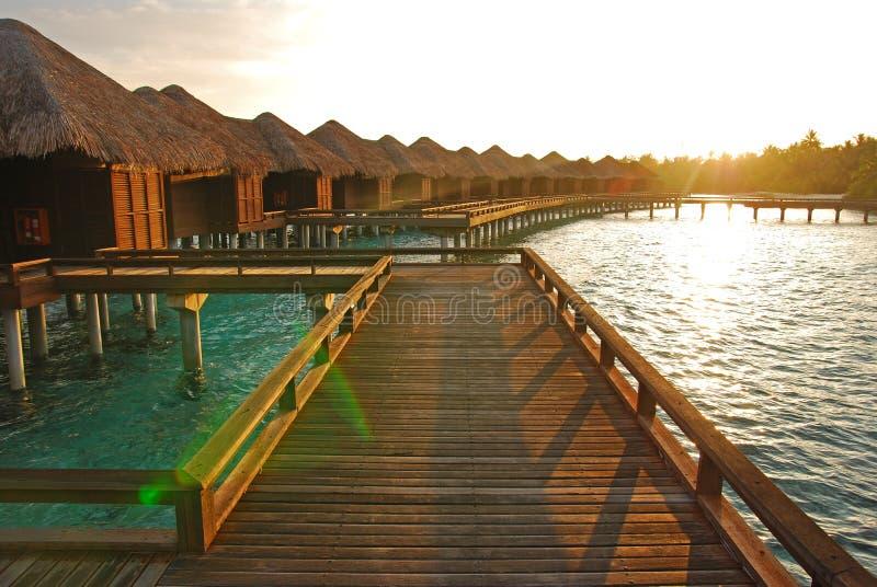 Sonnenaufgang mit dem Sonnenlicht, das auf das overwater Landhaus fällt stockbild