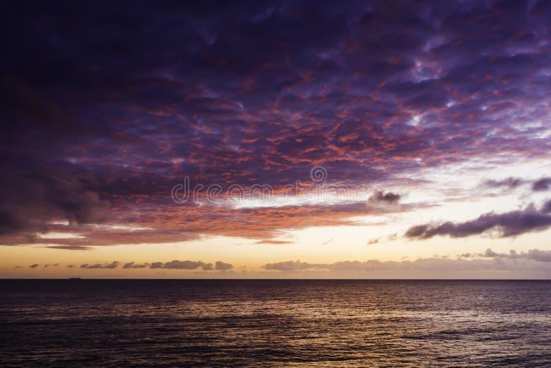 Sonnenaufgang mit drastischem Himmel über Meer lizenzfreie stockfotografie