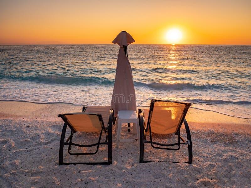 Sonnenaufgang mit Sonnenstühlen und -regenschirm auf der Küste am Marmorstrand auf der griechischen Insel Thasos im Ägäischen Mee lizenzfreies stockfoto
