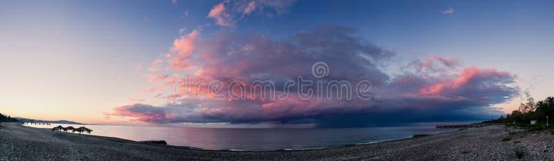 Sonnenaufgang mit Sturmfront auf dem Seestrand lizenzfreie stockbilder
