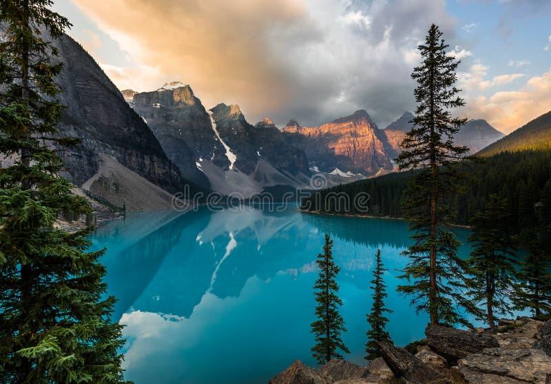 Sonnenaufgang mit Türkiswasser des Moraine Sees mit Sünde beleuchtete felsige Berge in Nationalpark Banffs von Kanada herein lizenzfreie stockfotos