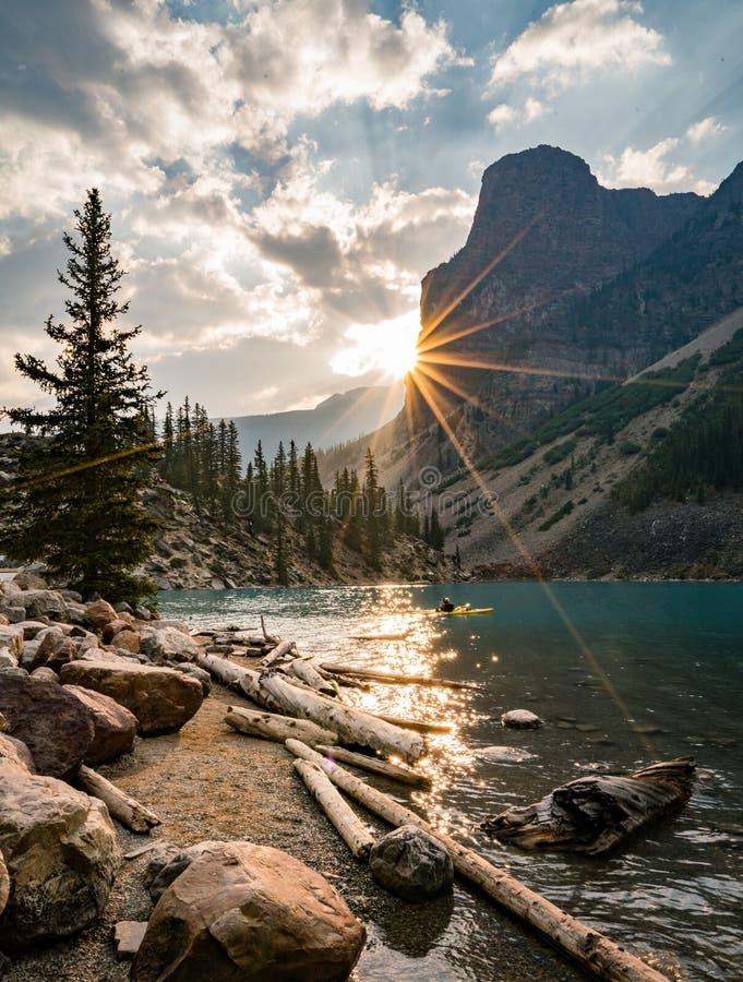 Sonnenaufgang mit Türkiswasser des Moraine Sees mit Sünde beleuchtete felsige Berge in Nationalpark Banffs von Kanada herein stockfotos