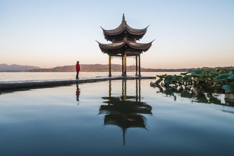 Sonnenaufgang Panoramasicht auf den Westsee in Hangzhou, China Girl-Silhouette in Sonnenaufgangsfarben lizenzfreie stockfotos