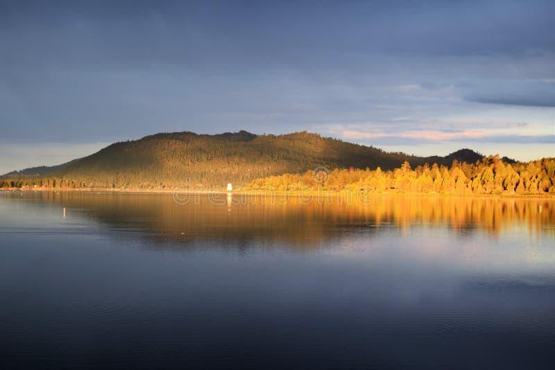 Sonnenaufgang verwandelt Pinienbäume Orangefarbene, ruhige Umgebung Mirrored Lake lizenzfreie stockfotografie