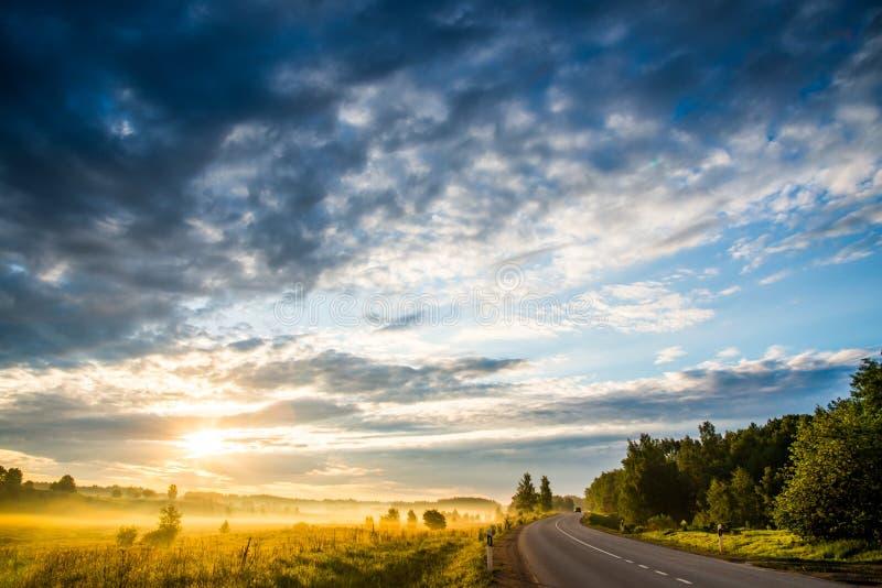 Sonnenaufganglandschaft des Himmels, der Straße und des Feldes lizenzfreies stockbild