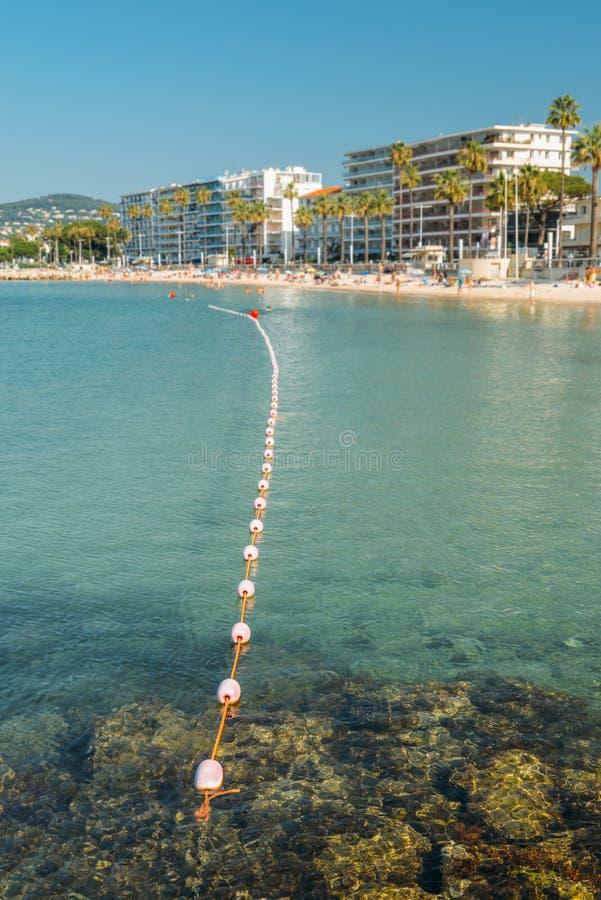 Sonnenbadegäste und -schwimmen des frühen Morgens setzen unidentifizierbare an den Juan-les Stiften, ein populärer Erholungsortbe lizenzfreies stockfoto