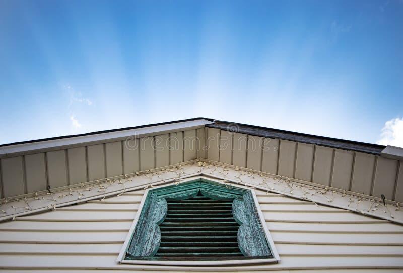 Sonnenbeschiene Strahlen, die hinter emporgeragtem Dach mit rustikalem blauem Fenster gl?nzen stockbild