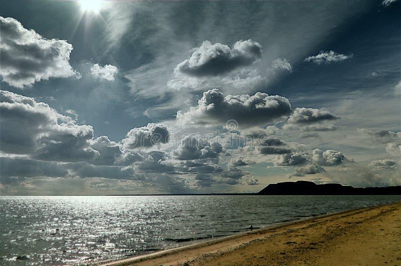 Sonnenbeschiener Himmel des Seestrandes in den Wolken, Lichtwellen, mit gelbem Sand stockfotos