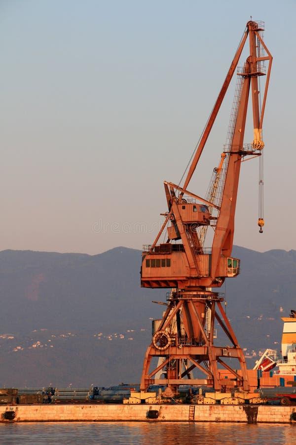 Sonnenbeschiener roter Hafenkran im leeren Morgenhafen von Rijeka Kroatien lizenzfreie stockfotos