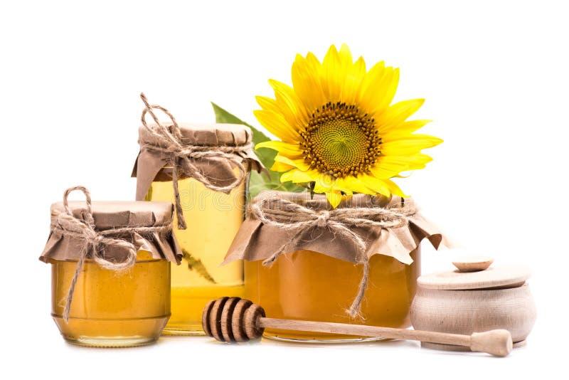Sonnenblume und Honig in den Glasgefäßen stockbild