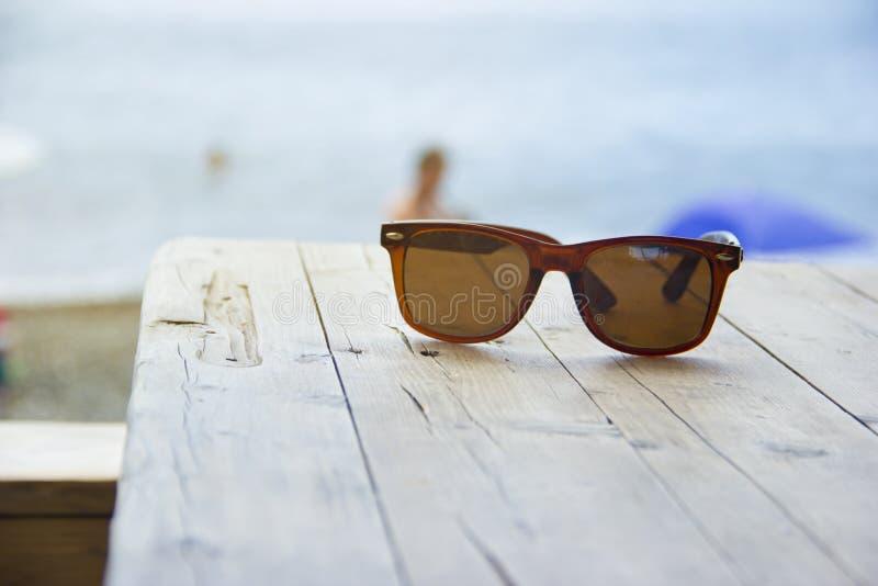 Sonnenbrille auf dem Tisch stockbild