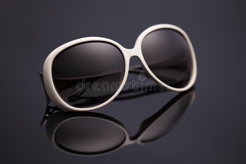 Sonnenbrille auf einem schwarzen Hintergrund stockfotos