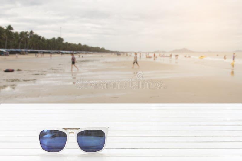 Sonnenbrille auf Holztisch mit Leuten auf dem Strand stockfotografie
