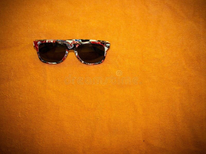 Sonnenbrille auf orange Tuch, ließ ` s zum Strand gehen lizenzfreie stockfotos