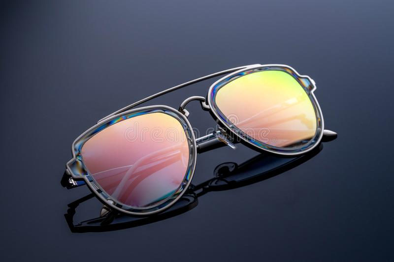 Sonnenbrille, Chamäleonfarbe, Schimmer in der Sonne Dunkler Steigungshintergrund lizenzfreie stockfotografie