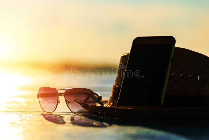 Sonnenbrille, Hut und Telefon sind aus den Grund und den Sonnenuntergang lizenzfreies stockfoto