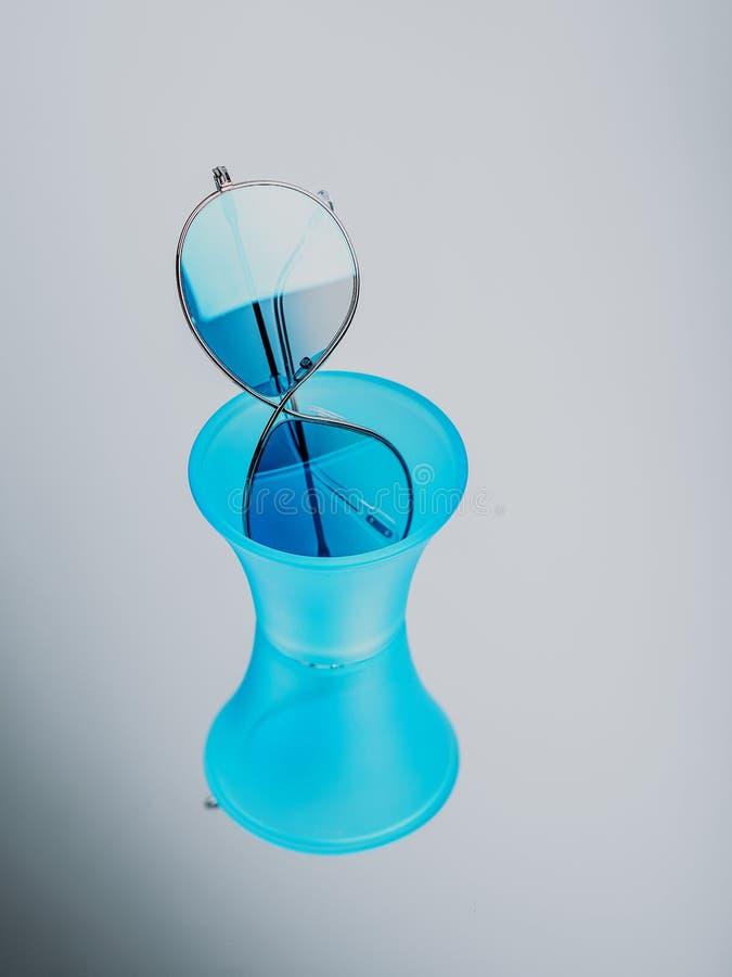 Sonnenbrille mit blauen Gläsern in einem blauen Plastikglas auf einem grauen Hintergrund lizenzfreies stockfoto