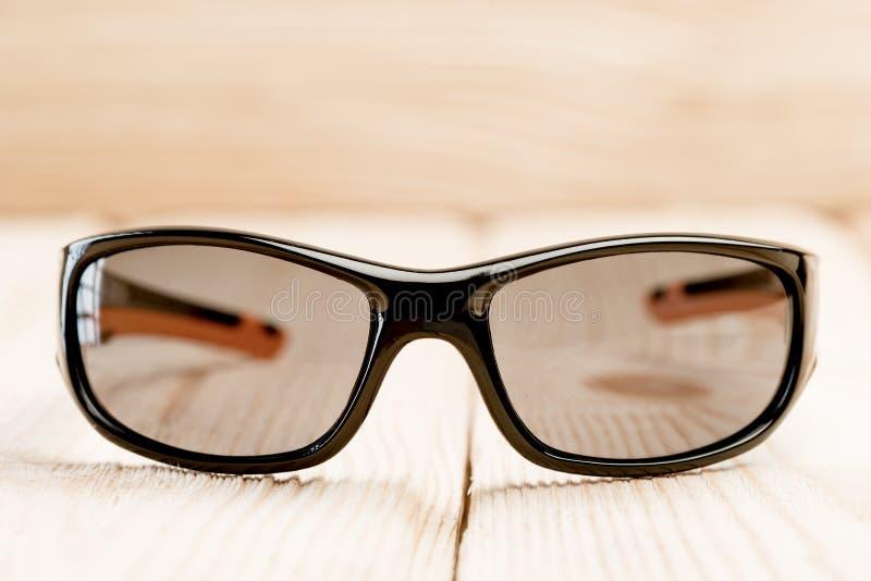 Sonnenbrille mit braunen Polarisierungsgläsern liegt auf einer Holzoberfläche stockbild