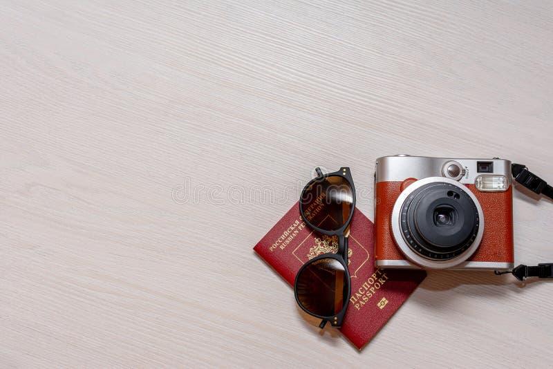 Sonnenbrille mit dem Pass eines Bürgers der Russischen Föderation und einer sofortigen Fotokamera auf einem weißen hölzernen Hint stockfotos