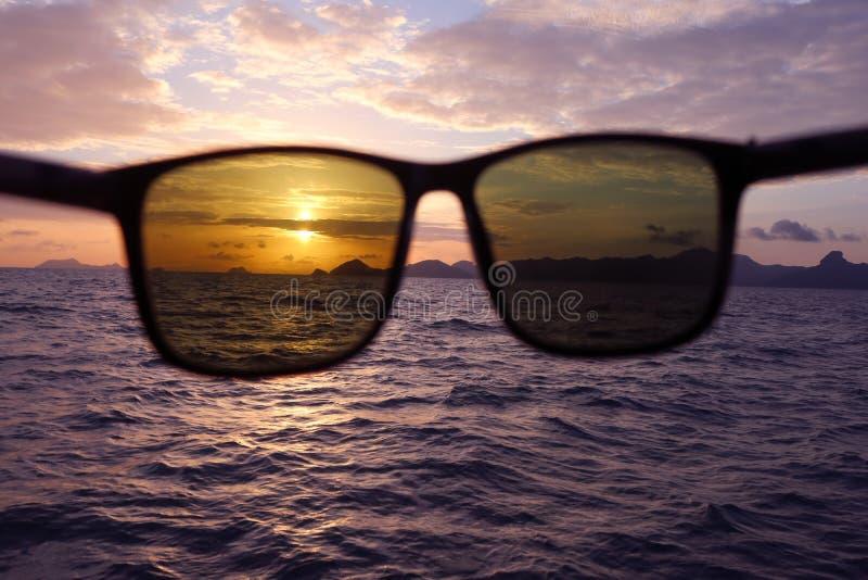 Sonnenbrille mit einem Sonnenuntergang im Meer lizenzfreie stockbilder