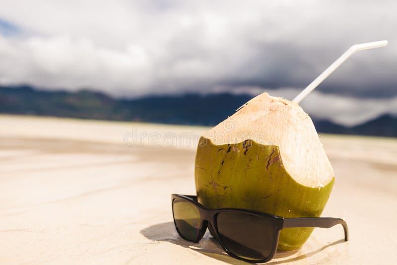 Sonnenbrille nahe Coconuß mit einem Stroh auf dem Strand stockbild