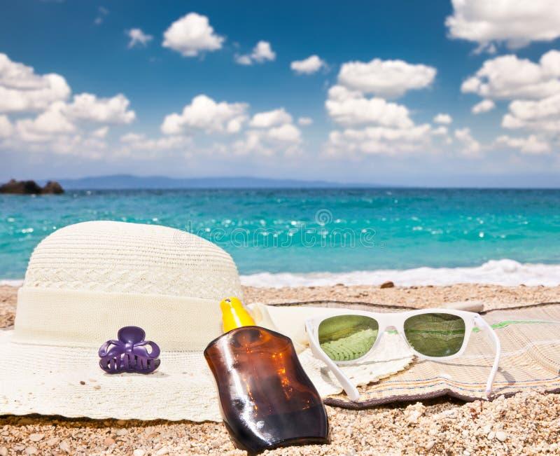 Sonnenbrille, sunsunhat, suncream auf Strand stockfotos