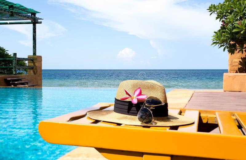 Sonnenbrille und Hut- und Swimmingpool mit Blume und dem Meer stockbild