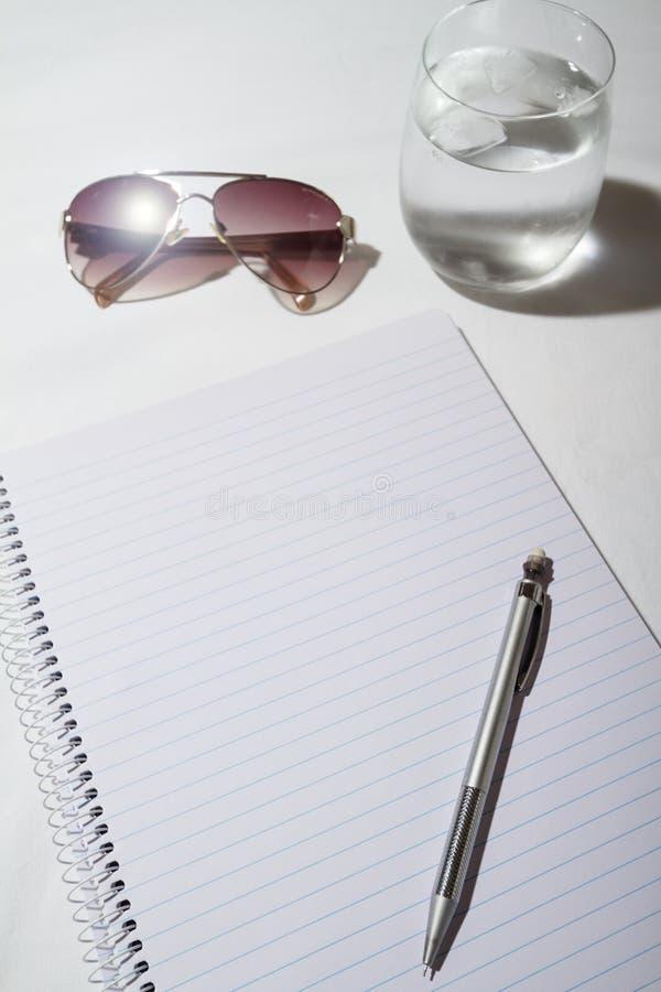Sonnenbrille, Wasser, Bleistift und Notizblock auf einer Tabelle von den Unkosten stockbild
