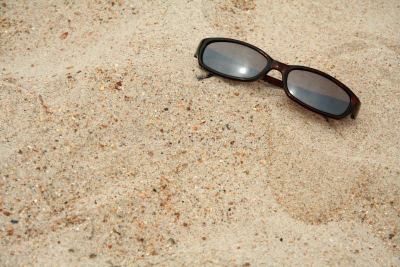 Sonnenbrillen im Sand stockbild