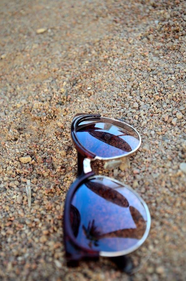 Sonnenbrillen im Sand lizenzfreies stockbild