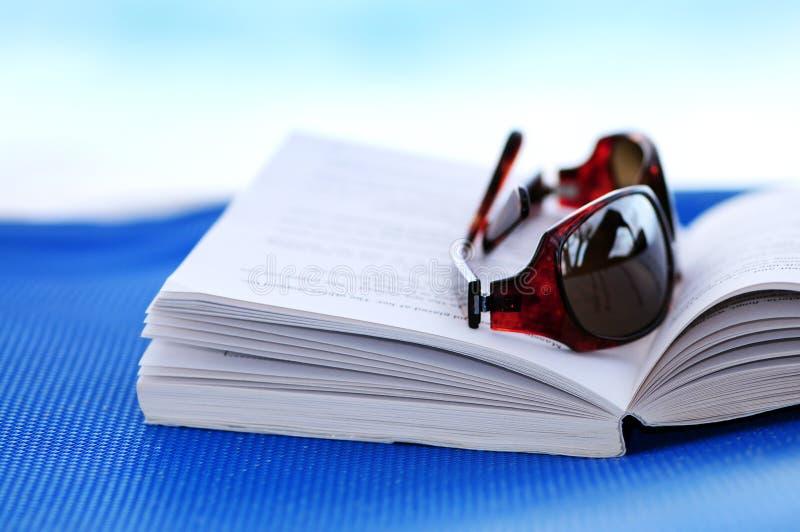 Sonnenbrillen und Buch auf Strandstuhl lizenzfreies stockbild