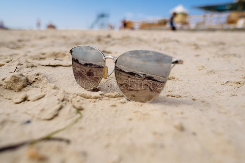 Sonnenbrillereflexion auf Meersandstrandurlaubferien lizenzfreie stockbilder