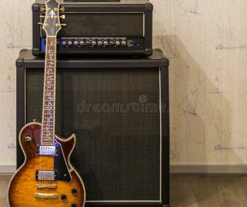 Sonnendurchbruche-gitarren-Stellung vor einem Verstärker und einem Klangeffektkasten, Berufsmusikausrüstung stockfoto