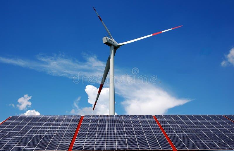 Sonnenenergie und Windmühle stockbild